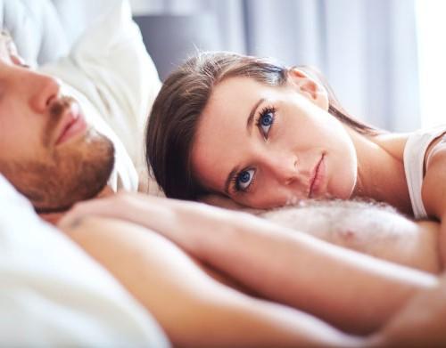 Pensive-woman-laying-on-sleeping-man