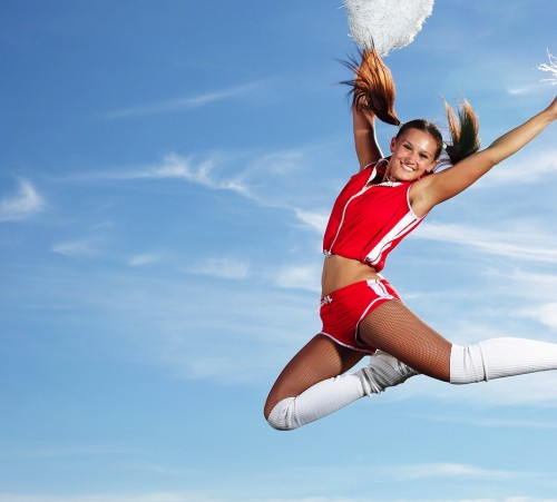 Young-beautiful-female-cheerleader-in-uniform-jumping-high
