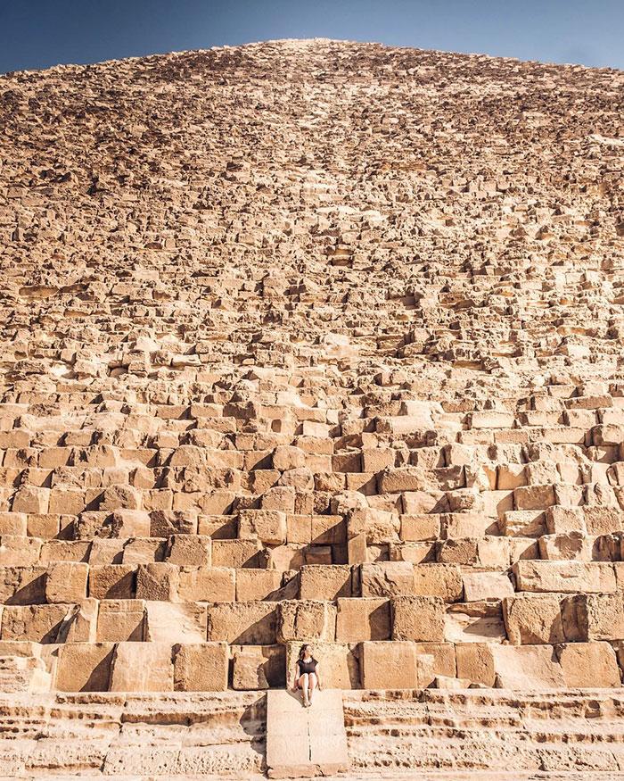 Kona situr á þrepum pýramída í Giza
